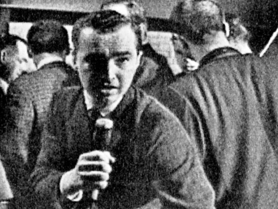 Reporter Bob Huffaker speaking into microphone