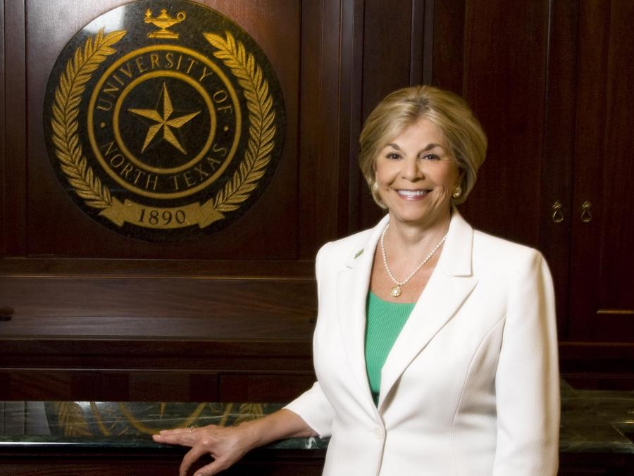 <p>Gretchen Bataille standing in front of UNT seal</p>