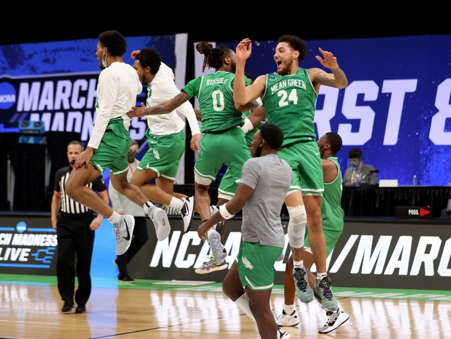Mean Green men's basketball jumps into the air after beating Purdue in the first round of the NCAA championship.