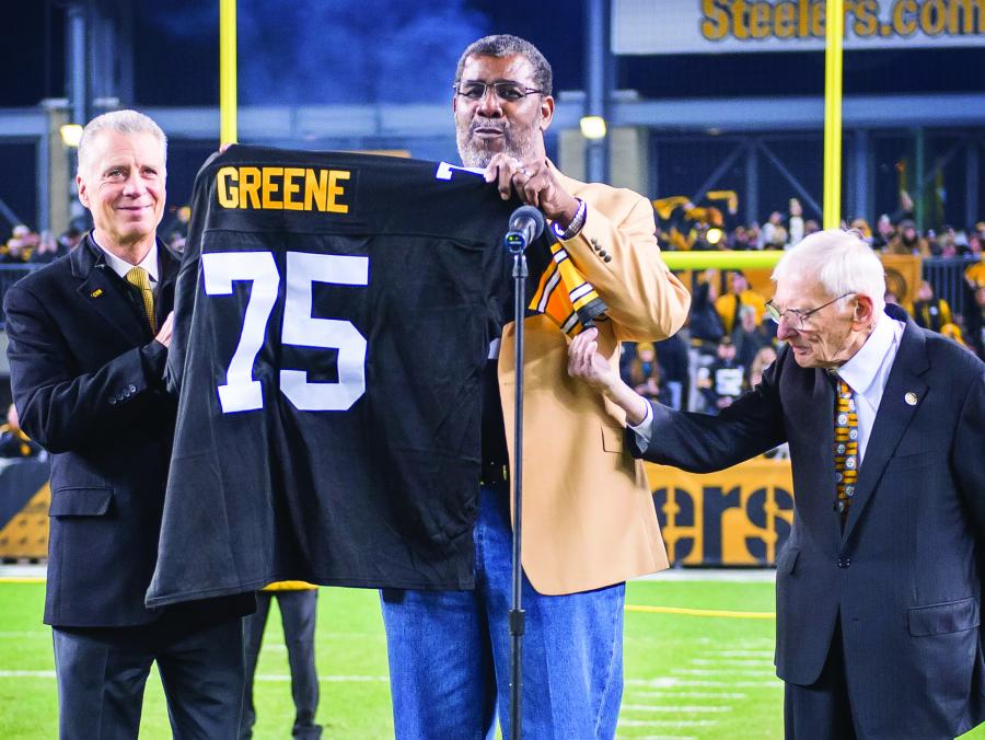 <p>Mean Joe Greene holding jersey</p>