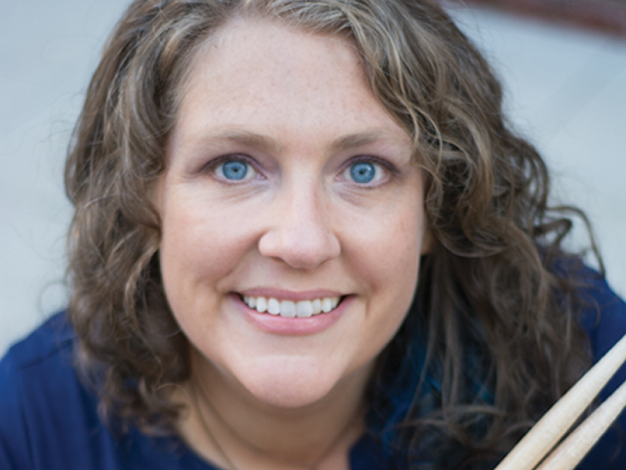 Michelle Schusterman holding a snare drum and drumsticks