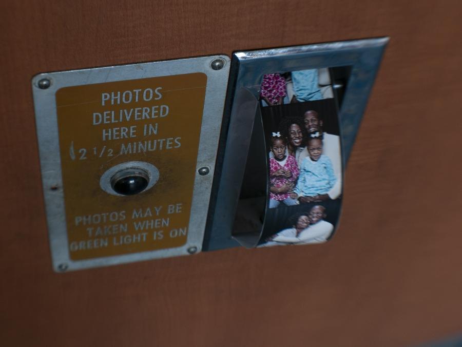 <p>Pictures of Pineset-Bryant family sliding out of photo booth</p>