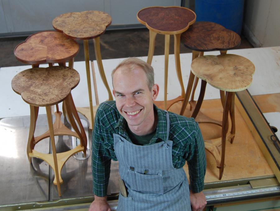 <p>Austin Heitzman in front of handmade furniture</p>