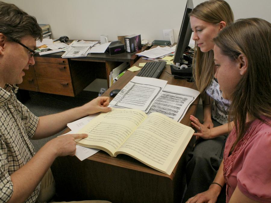 <p>Professor Schulze reading book with students</p>