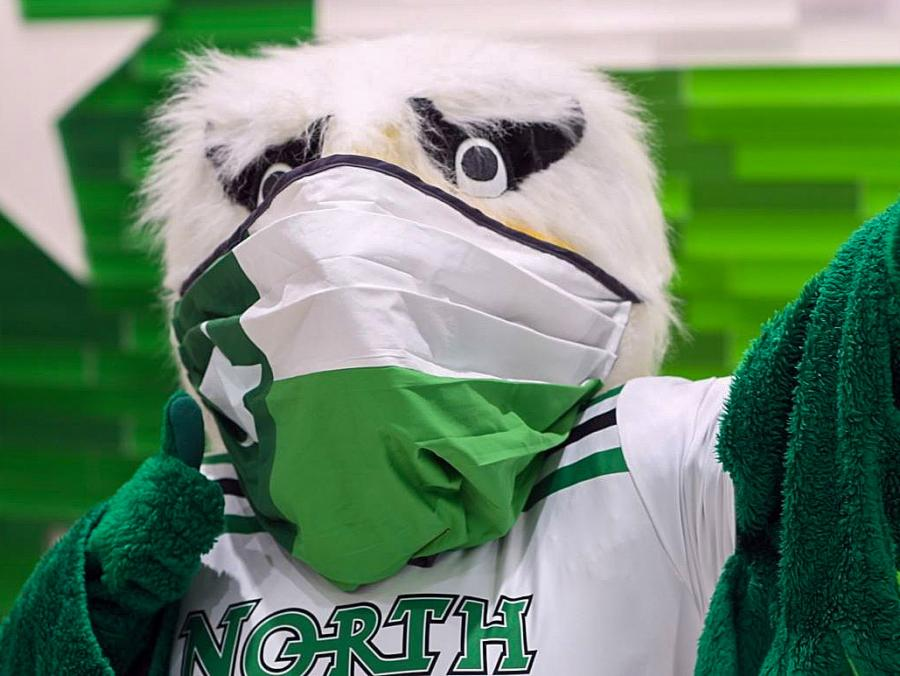 UNT's Scrappy Mascot wears his mask and gives a thumbs up