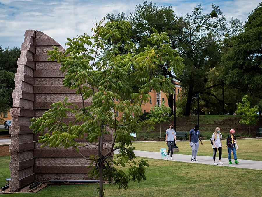 "Picture of students walking outside of UNT campus with the sculpture ""Shield"" in the foreground and trees on both sides."