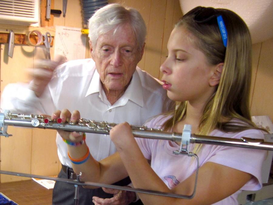 "<p>Clarence ""Woody"" Wood showing flute to Abby Gieseke</p>"