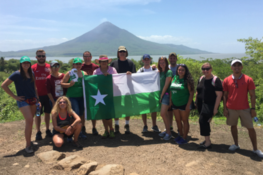 Students hold up the UNT battle flag as part of a study abroad trip to Nicaragua sponsored by UNT and Explore Study Abroad, an Austin-based business owned by alumnus Anthony Spence ('03 M.S.).
