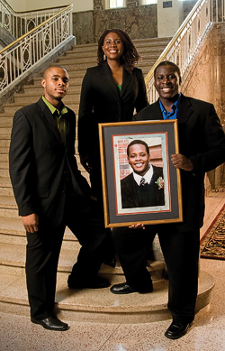 The Uduebor family in the Hurley Administration Building, (left to right) Valentine Uduebor ('08), Cynthia Uduebor ('00) and Lovett Uduebor with a photo of their brother, Otis ('06). (Photo by Jonathan Reynolds)